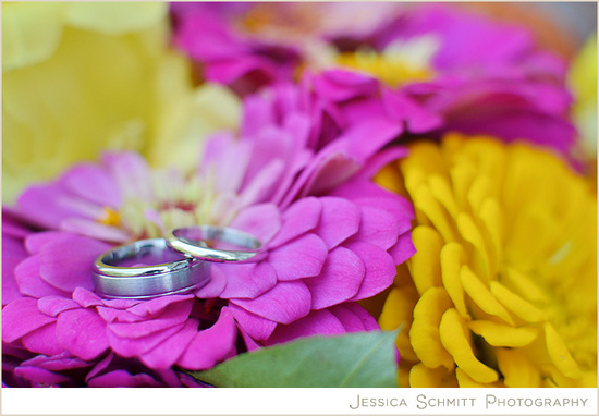 photo of Wedding ring shot atop bright zinnia flowers