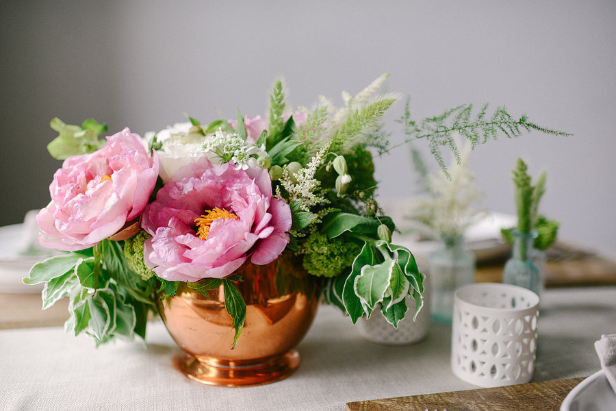 Wedding centerpiece of pink peonies and leaves in copper vase