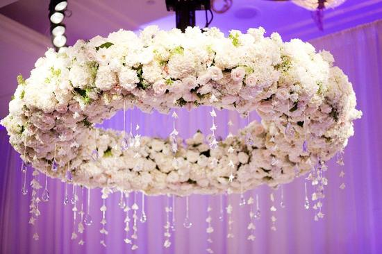 Floral chandelier at wedding reception with delicate hanging crystals