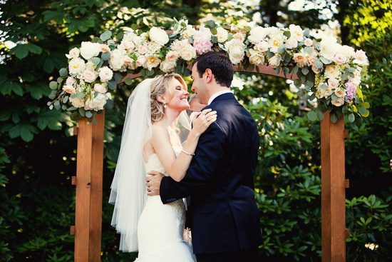 Bride and groom kiss beneath rose adorned arbor