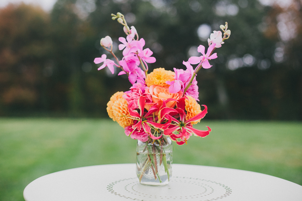 Exotic-wedding-centerpiece-with-bright-orchids-and-orange-blooms.full
