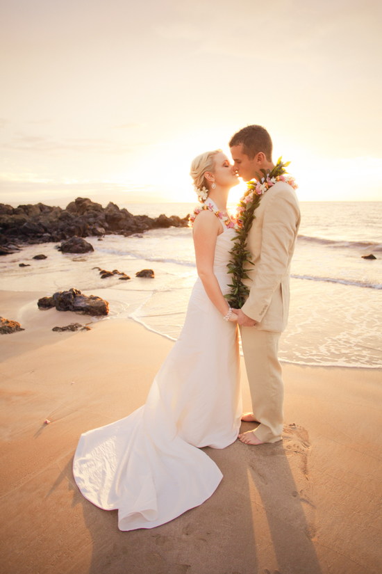 Bride and groom kiss on beach with beautiful sunset in back