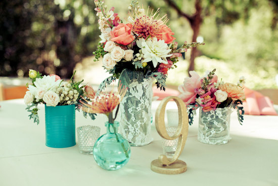 Lace covered wedding vases with gold table numbers