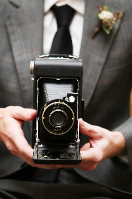 Dapper groom holds vintage camera