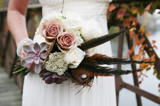 Gorgeous wedding bouquet with roses succulents and feathers
