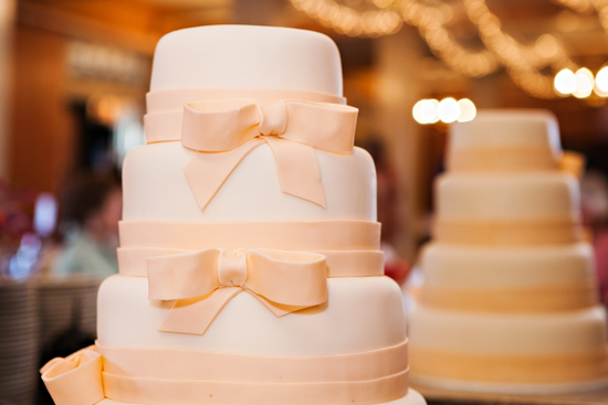 Ivory and pastel peach wedding cake with ribbon bows design