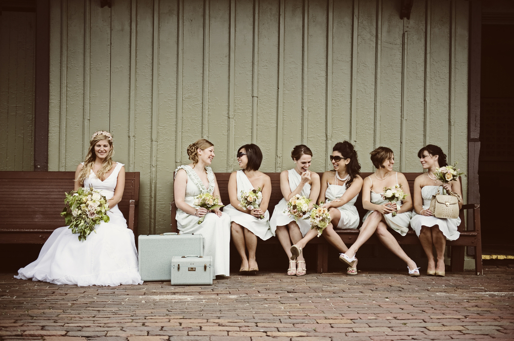 Vintage-mix-and-match-bridesmaids-chat-on-bench.full