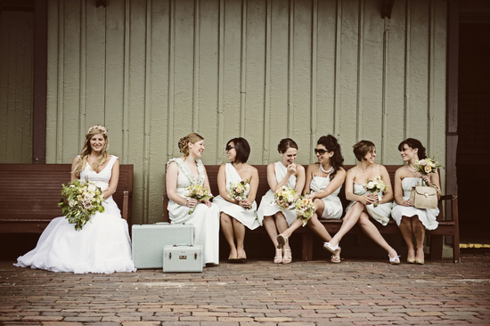 Vintage mix and match bridesmaids chat on bench
