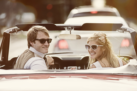 Retro bride and groom drive off in antique ride
