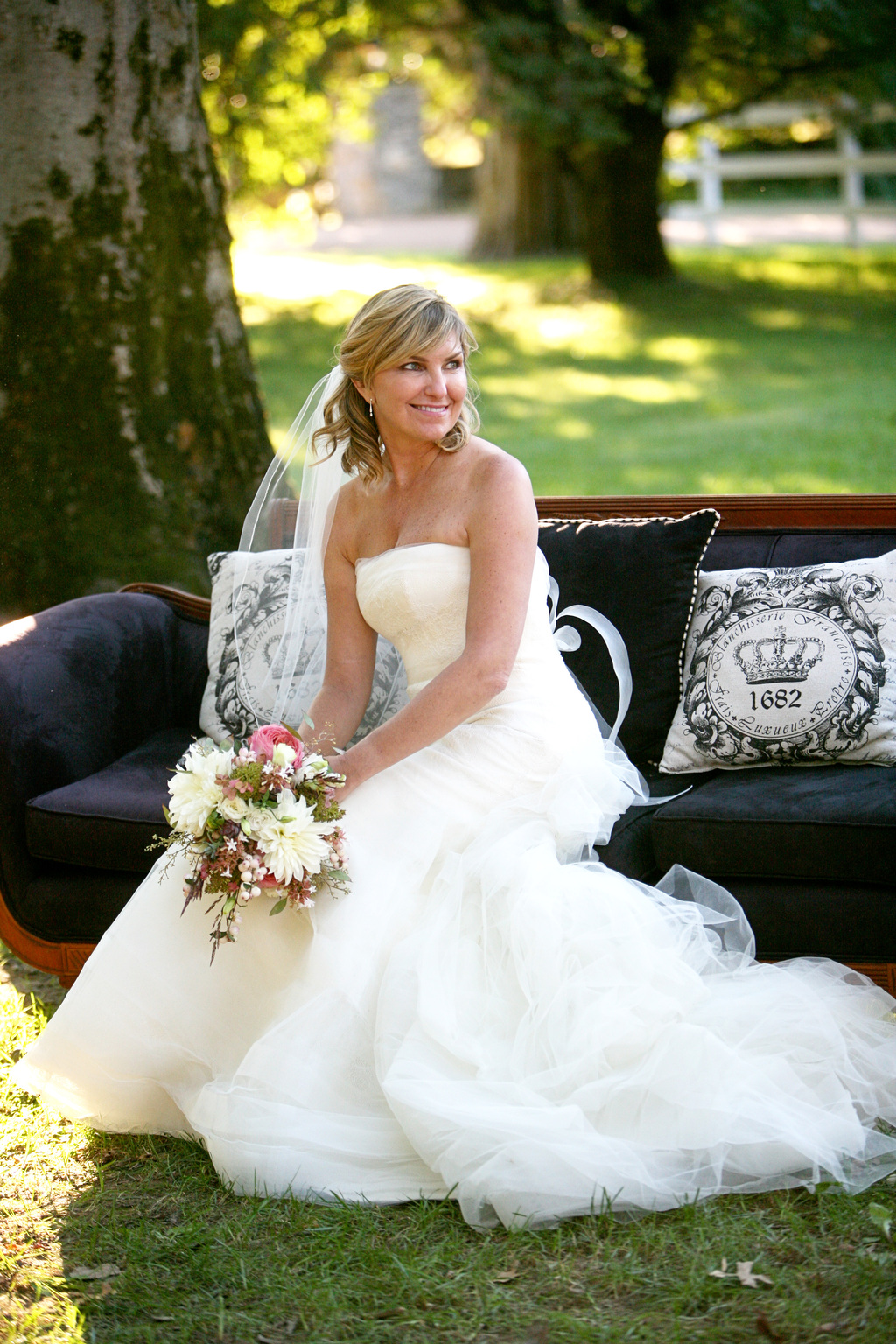 Southern bride poses outdoors on vintage couch