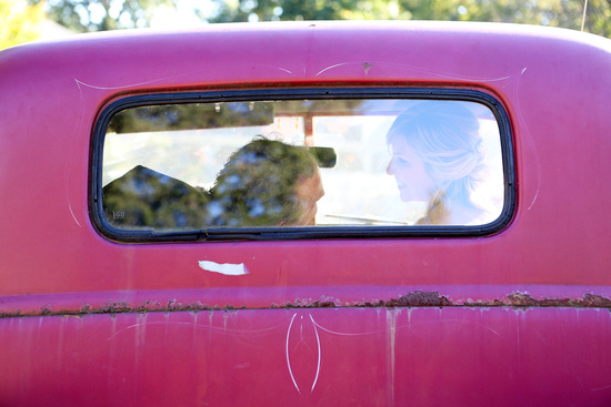 bride and groom in an old pink pickup