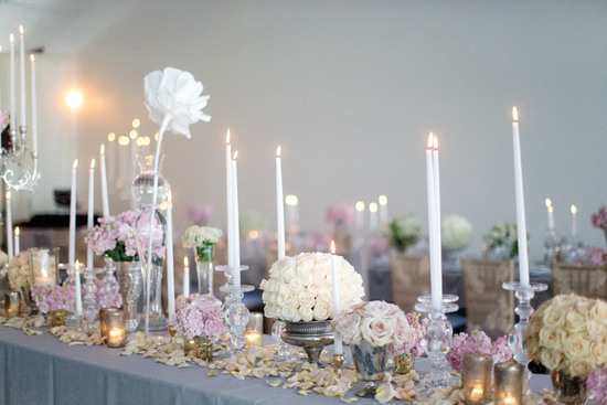 Romantic wedding tablescape with elegant rose centerpieces and taper candles