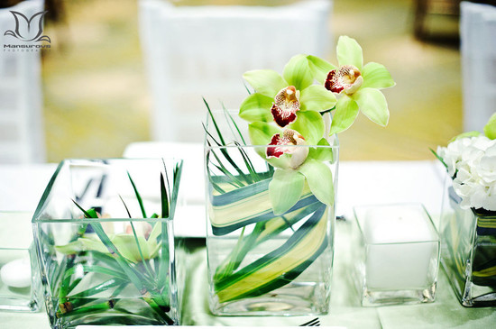 Modern wedding reception centerpieces with lime green and ruby orchids