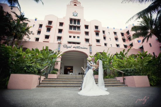 royal hawaiian honeymoon giveaway destination wedding- bride and groom kiss with venue in back