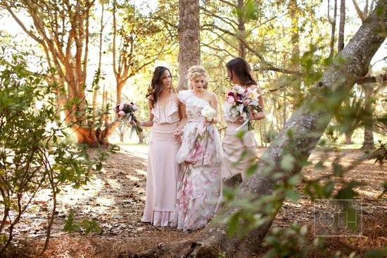 Romantic summer bride walks with bridesmaids through the woods