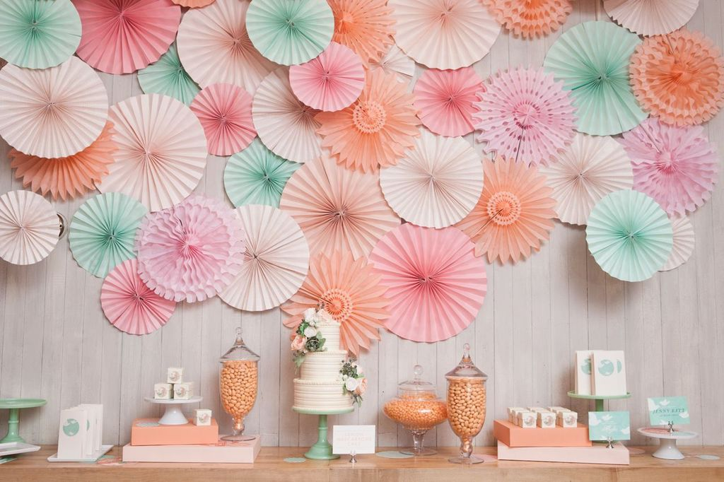 Pastel wedding backdrop behind reception cake sweets table