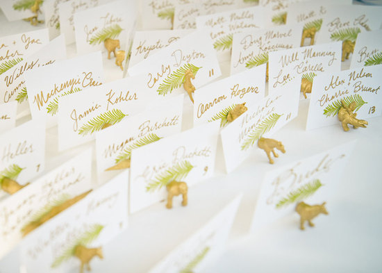 Tropical wedding escort cards with fun gold animal holders