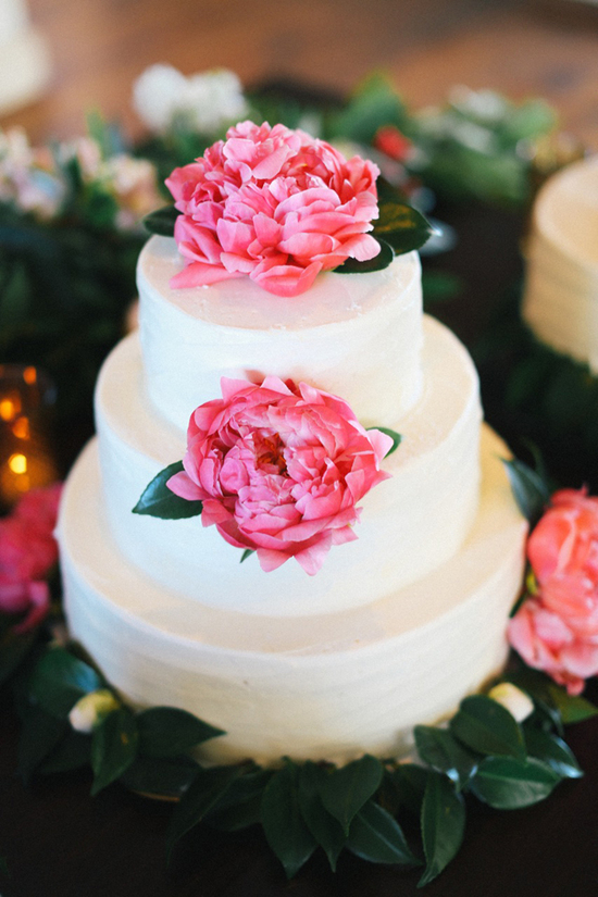 White wedding cake topped with bright pink peonies