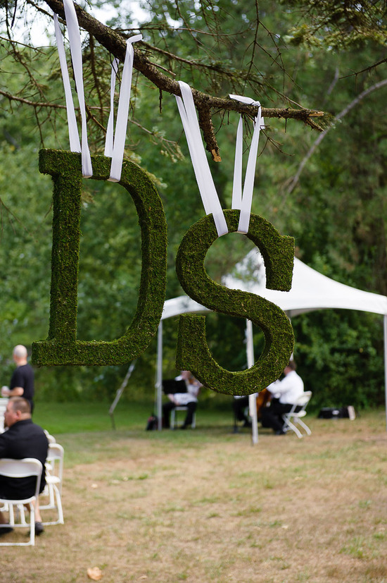 Moss wedding initials hang from tree with white ribbon