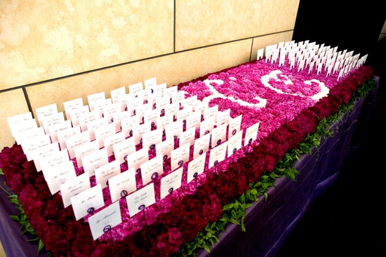 Floral covered escort card table with bride and groom initials