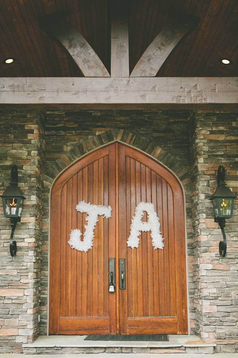 White-floral-initials-hang-on-wedding-ceremony-doors.full