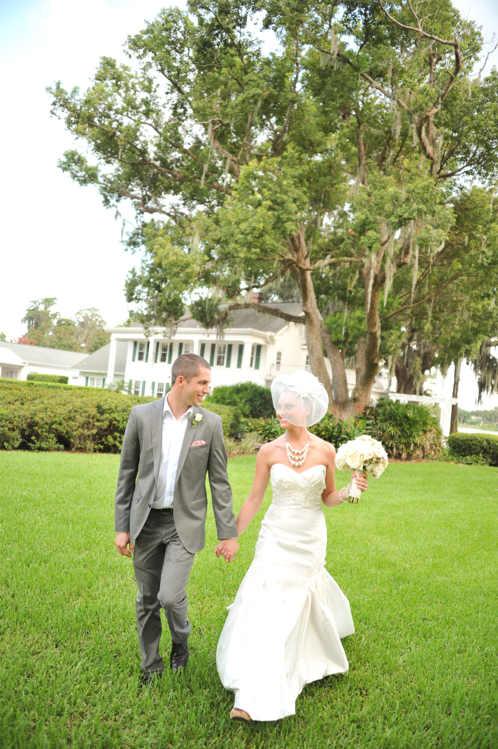 Bride-and-groom-walk-hand-in-hand-at-outdoor-florida-venue.full