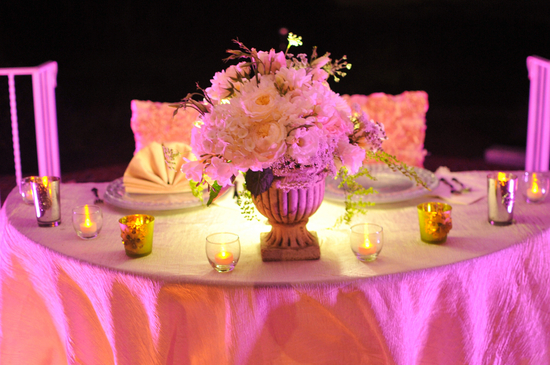 Pink lighting adds enchantment to wedding sweetheart table