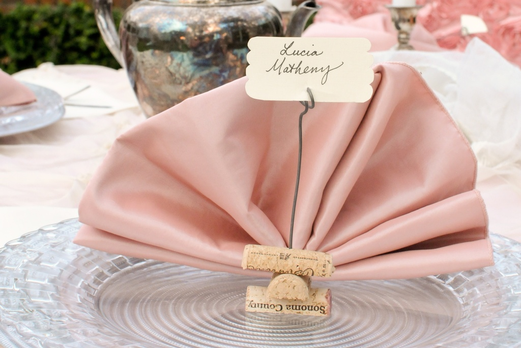 Pink wedding napkins with wine cork escort holders