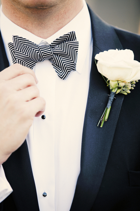 Classic groom wears tux with zig zag bow tie