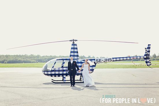 Bride and groom pose in front of checkered helicopter