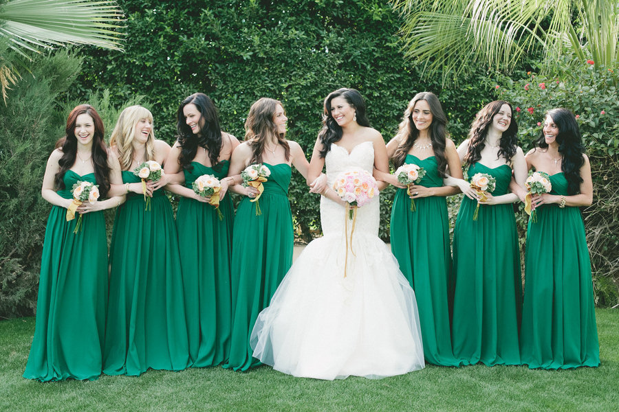 Bride wears white mermaid wedding dress bridesmaids in emerald green