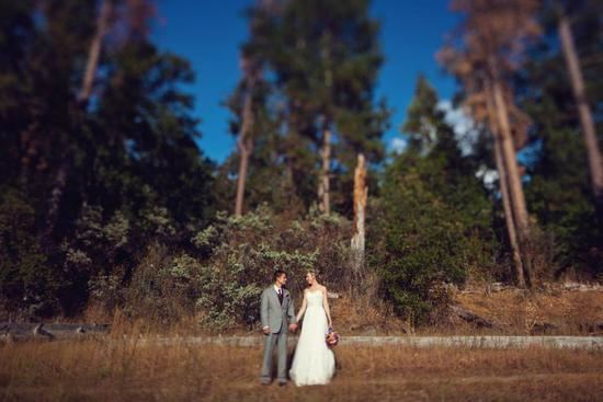 Glamping wedding theme bride and groom pose with forest in back