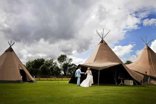 Bride and groom walk towards teepee during outdoor wedding