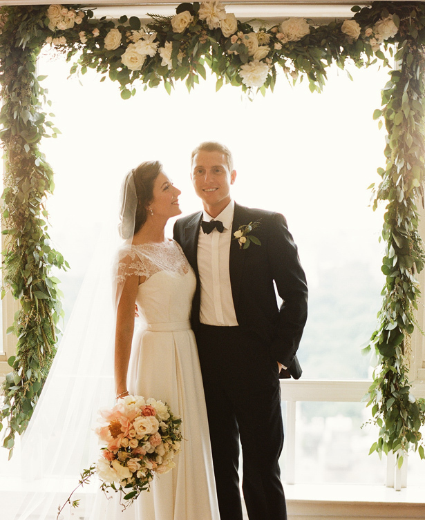 Classic New York bride and groom pose beneath floral adorned arbor