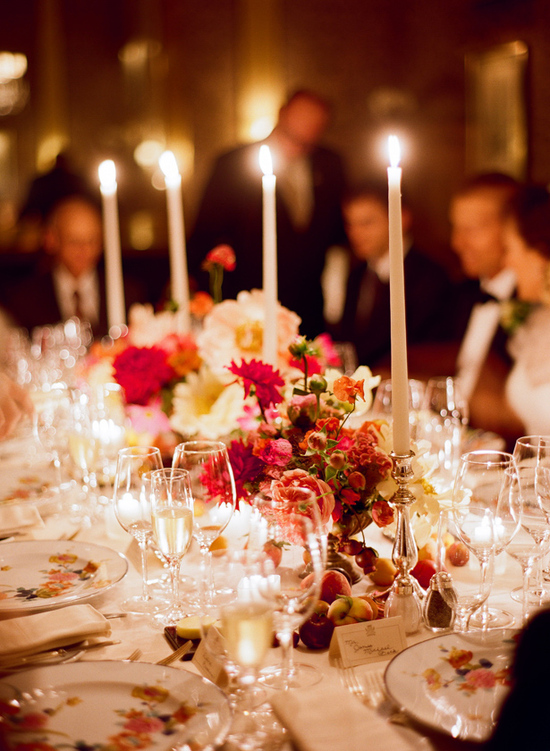 Romantic wedding reception table with deep pink flowers and taper candles