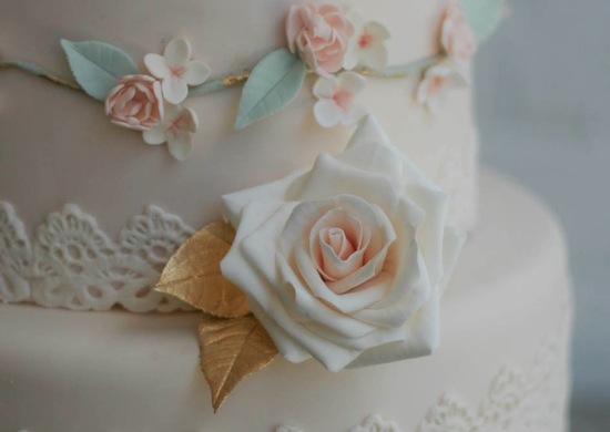 Romantic blush pink wedding cake with gold leaves