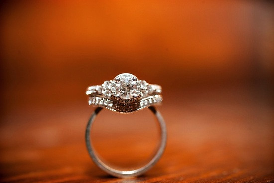 Diamond engagement ring and wedding band balance on grooms ring