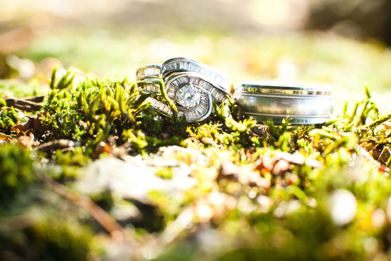 engagement ring and wedding band photographed on mossy decor