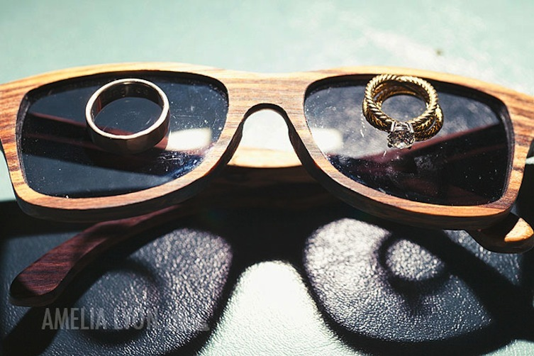engagement ring and wedding bands photographed on retro sunglasses