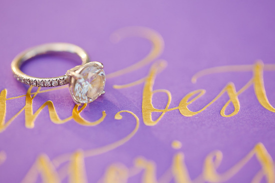 Dazzling engagement ring shot on purple and gold invitations