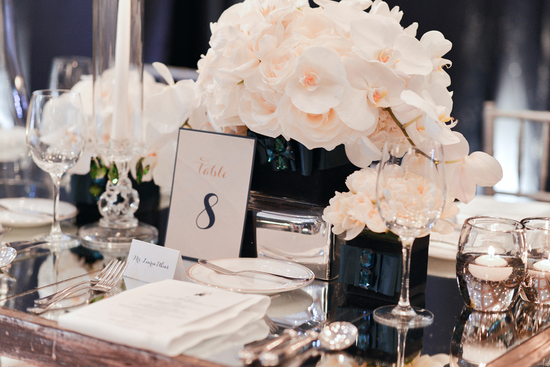 White orchids in emerald vases at elegant wedding reception