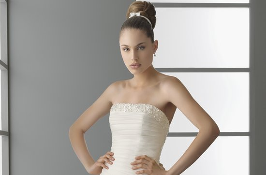High bridal bun accented with a white ribbon