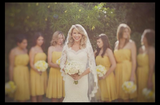 Bride wears lace wedding dress, bridesmaids in yellow