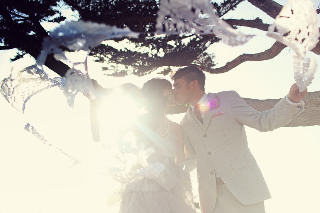 incredible wedding photography by Max Wanger bride and groom kiss beneath a tree
