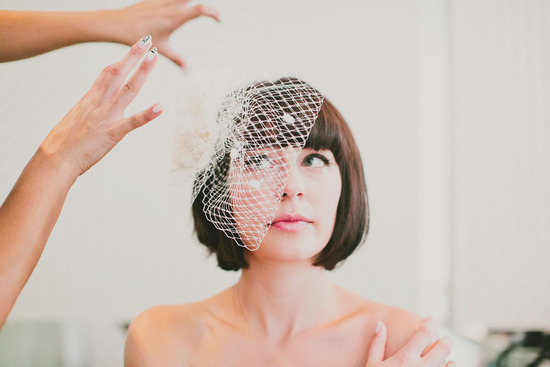 Sleek bob wedding hairstyle paired with a retro birdcage veil with dotty accents