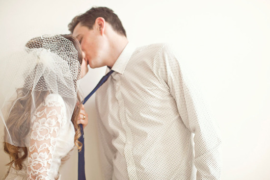 Vintage bride wears sleeved lace wedding dress and pouf veil