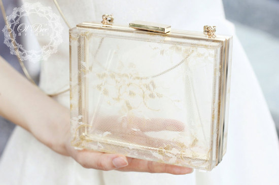 transparent bridal clutch with gold and lace details