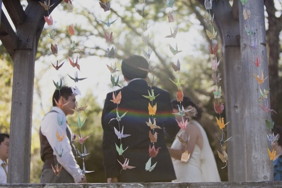 Colorful paper origami cranes create whimsical wedding ceremony backdrop