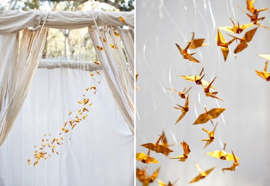 gold origami cranes decorate outdoor wedding arbor