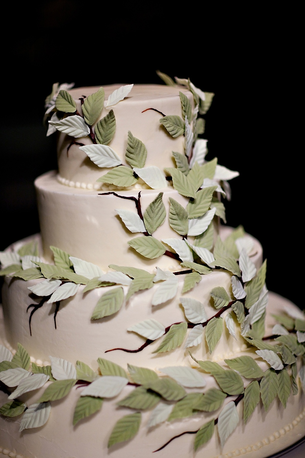 Elegant ivory wedding cake adorned with sugar leafs